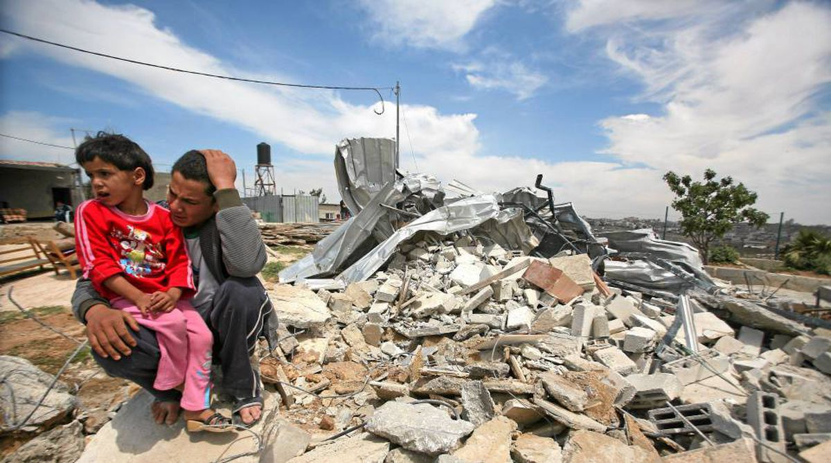 Relatives of Palestinian Ali Salim sit on the rubble of his house in the West Bank village of Al-Khader. The house was demolished by Israeli troops because it was too close to Israel's controversial separation barrier.