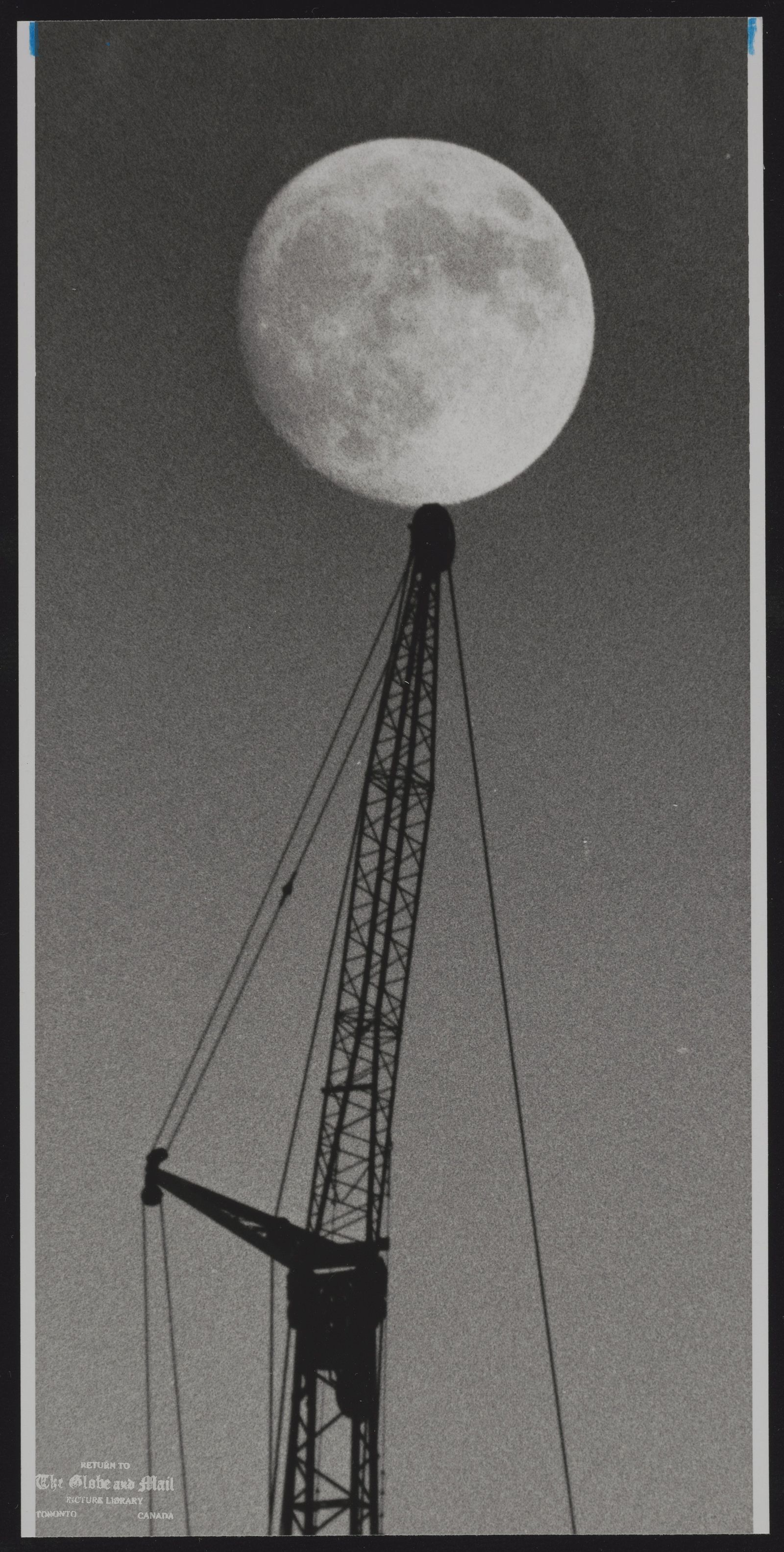 MOON THE MOON APPEARS TO BE VERY DELICATELY BALANCED ON A CRANE AT THE SITE OF SKYDOME CONSTRUCTION.