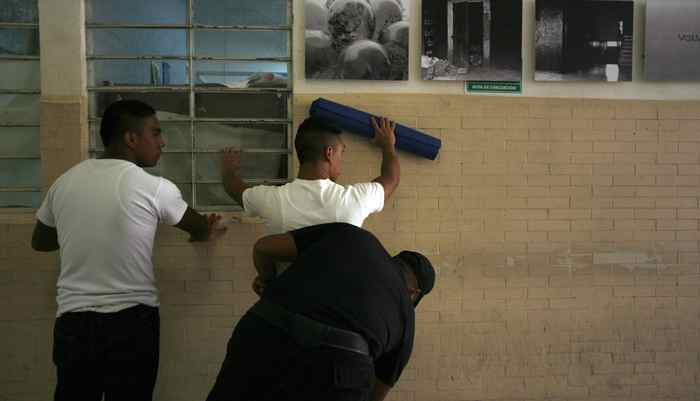 Inmates are being frisked by a security guard before a yoga class at a juvenile detention centre in Mexico City November 16, 2011.