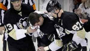 Pascal Dupuis, centre, is helped from the ice by teammates Sidney Crosby, right, and Bill Guerin after he was run into the boards in the third period of their NHL hockey game against the New York Islanders in Pittsburgh on Tuesday night.