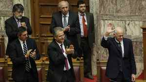 Lawmakers applaud Greek Prime Minister George Papandreou, right, as he waves after his speech during a parliament session in Athens on Thursday.