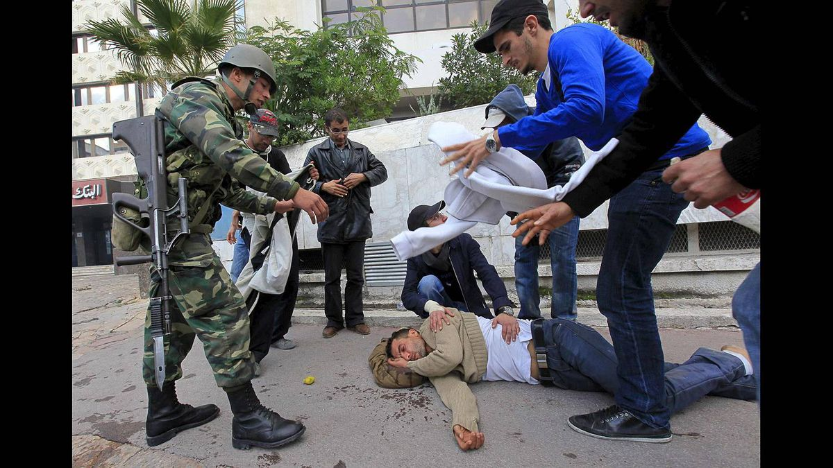 A Tunisian soldier and rioters look at a rioter who lost consciousness after tear gas was released during clashes with the police in downtown of the capital Tunis