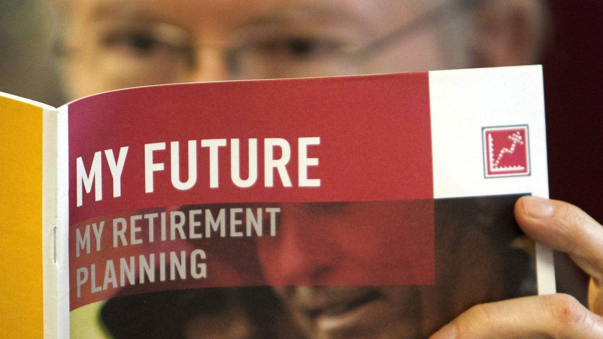 A man looks over a brochures offering various retirement savings options Friday, February 3, 2012 in Montreal.