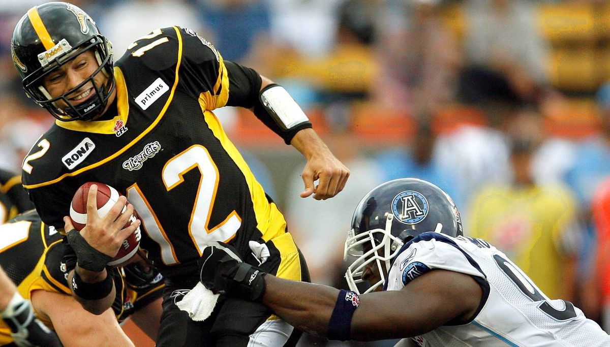 Hamilton Tiger-Cats quarterback Quinton Porter is sacked by Toronto Argonauts defensive end Ronald Flemons (R) during the first half of their CFL football game in Hamilton.