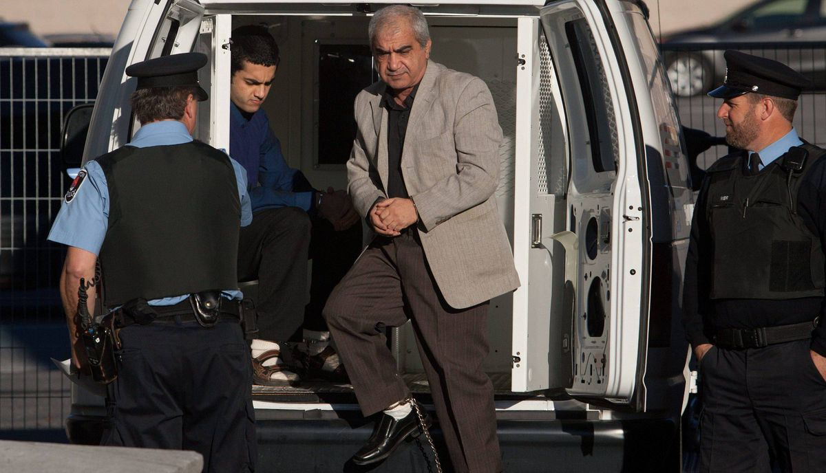 """Mohammad Shafia and Hamed Shafia step out from the police van at the Frontenac county courthouse in Kingston, Ont., on Monday Nov. 21, 2011. The Afghan-Canadian businessman, along with his second wife and his eldest son, were the defendants in a sensational """"honour killings"""" trial last year at Kingston's Frontenac County Courthouse. Convicted in the murder of his first wife and three of his daughters, the family patriarch and his son were sent to the Kingston Penitentiary, five minutes away from the courthouse."""