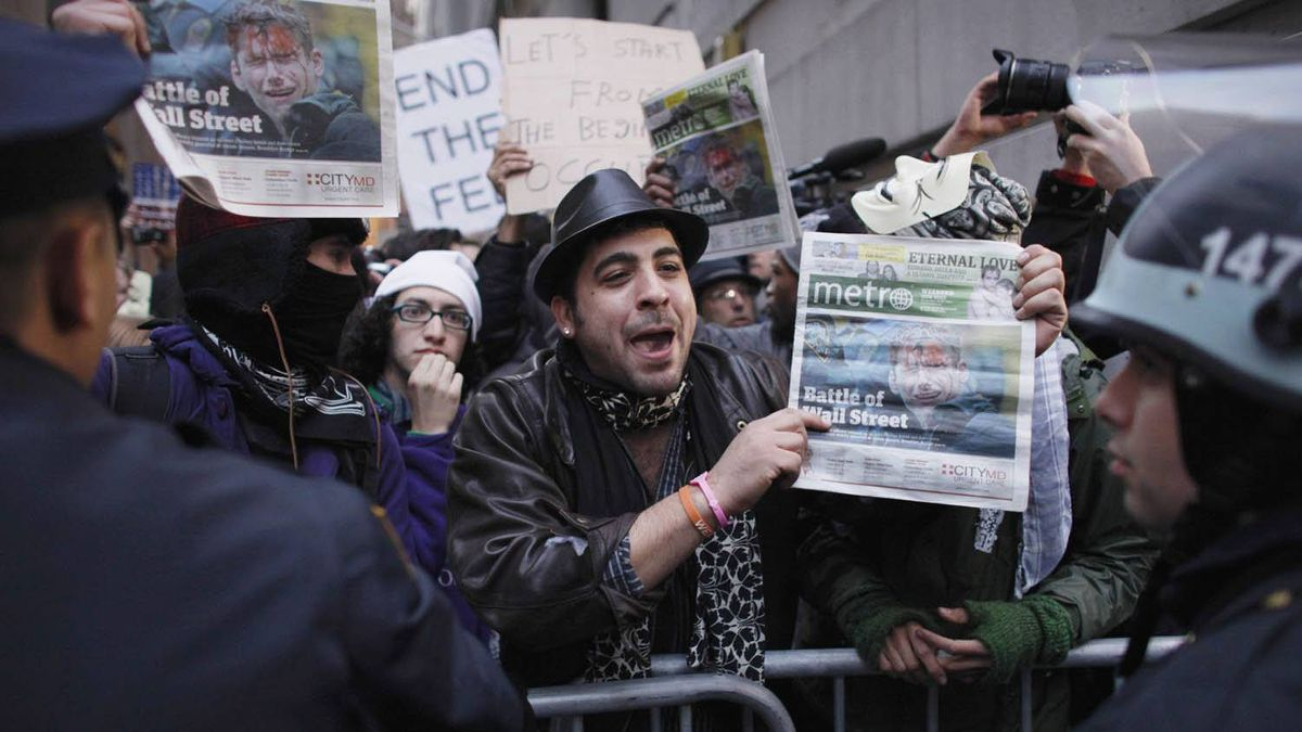 Protesters affiliated with the Occupy Wall Street movement show local newspapers to police officers while they march to the New York Stock Exchange Nov. 19, 2011.