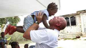 HMCS Halifax Petty Officer Andy Cotterill plays with Felicity, 2, at the Faith and Love in Action Orphanage in Jacmel, Haiti. Cotterill met the young girl at an orphanage the crew of the Halifax was working at in Jacmel following the earthquake. He fell in love with the little girl and wants to adopt her.