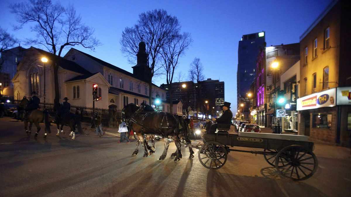A horse-drawn carriage with priod-style casket and pallbearers leads the memorial procession for the Titanic victims in Halifax on Saturday night.