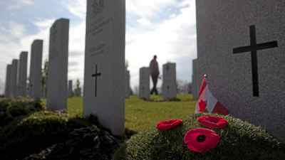 Poppies are seen at the foot of a tombstone in Beechwood National Military Cemetery as a man walks past in Ottawa on Sunday, November 7, 2010.