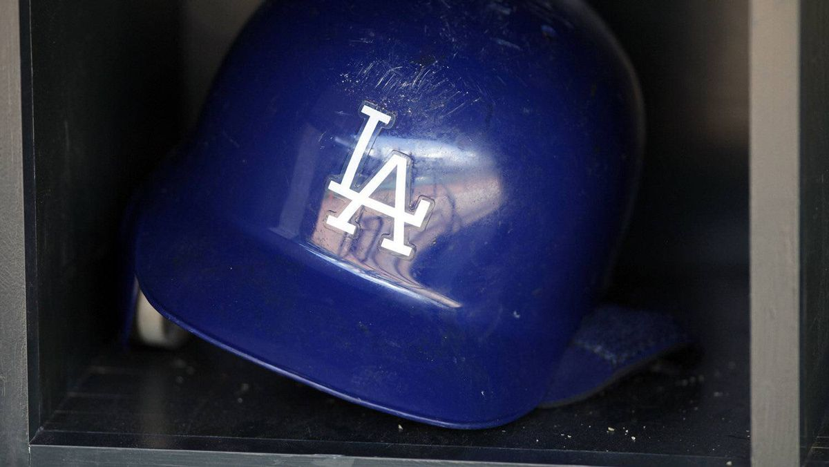 A batting helmet reflects the dugout of the Los Angeles Dodgers before the start of the Dodgers' American League MLB baseball game against the Minnesota Twins at Target Field in Minneapolis in this June 27, 2011 file photograph. The Los Angeles Dodgers baseball team said on November 2, 2011, it has agreed with Major League Baseball (MLB) officials to a court-supervised sale of the team and its media rights, potentially ending a long-running court battle between the league and owner Frank McCourt. Picture taken June 27, 2011. REUTERS/Eric Miller/Files