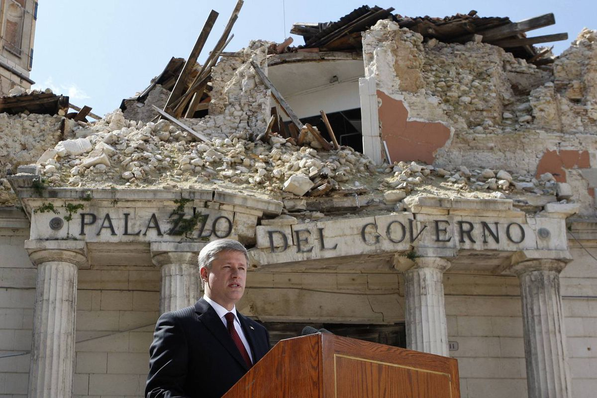 Canada's Prime Minister Stephen Harper speaks in front of buildings destroyed in the April earthquake in L'Aquila, Italy, on July 8, 2009.