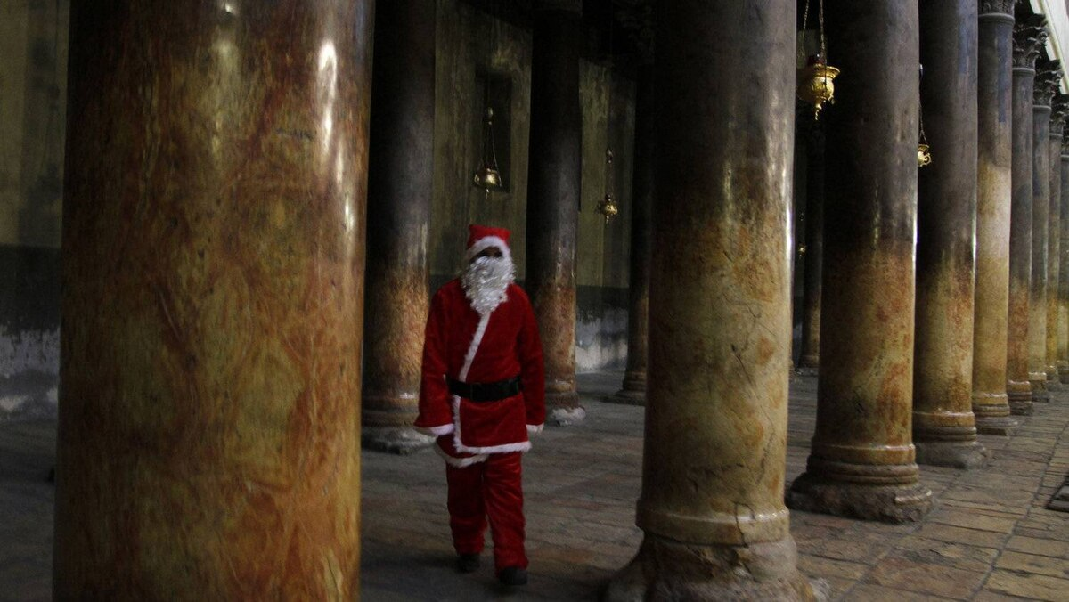 A Palestinian Christian dressed as Santa Claus walks through the ancient columns in the Church of the Nativity in the biblical West Bank city of Bethlehem.