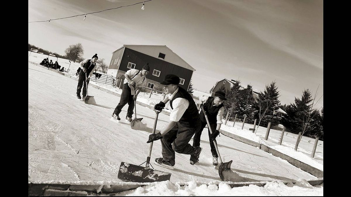 It's a group effort to scrape the ice whenever the need arises during a game of shinny played by some Mennonite boys in Wallenstein, Ontario on Jan 8, 2011. (Photo by Peter Power/The Globe and Mail)
