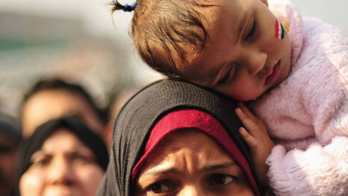 A girl with an Egyptian flag painted on her face sleeps on her mother's shoulder during a demonstration against the Egyptian military council in Tahrir square in Cairo December 2, 2011.