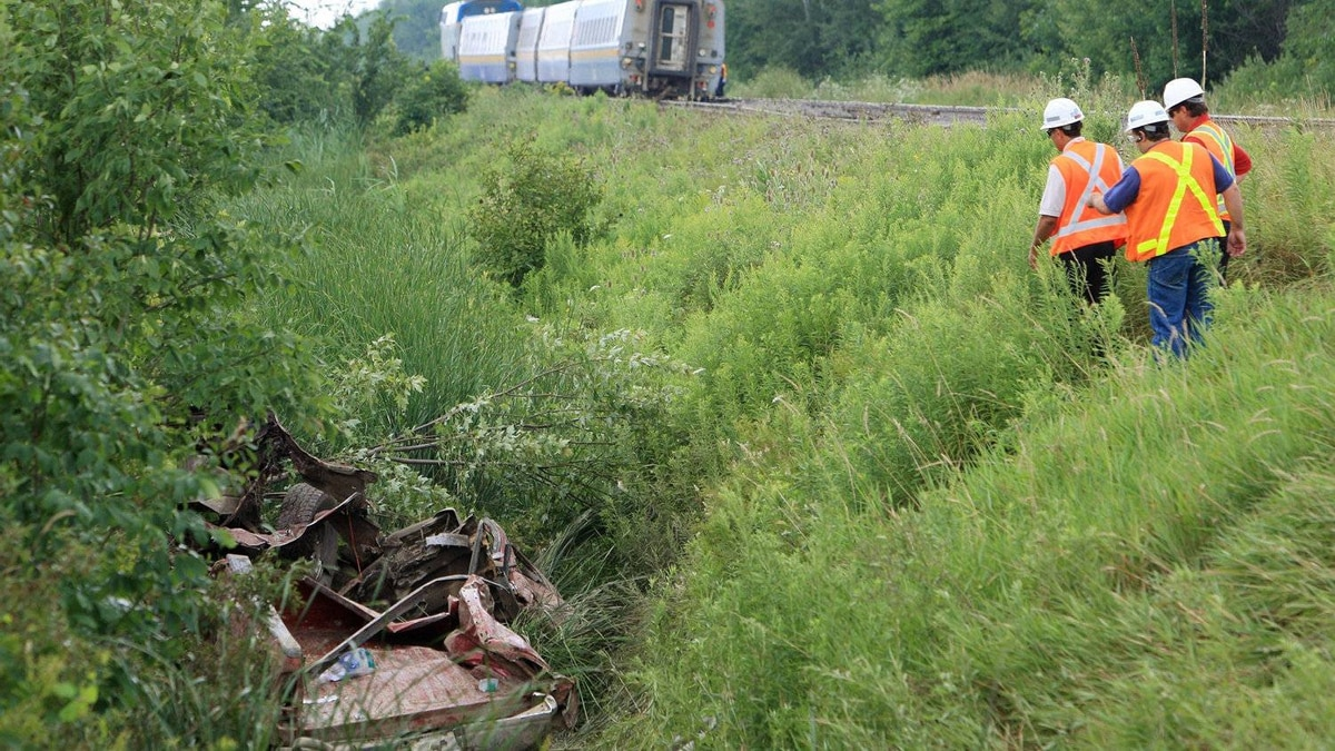 Investigators look over the scene where seven people were injured when a pick-up truck collided with a westbound VIA passenger train west of Glencoe, Ont., Friday, July 29, 2011.