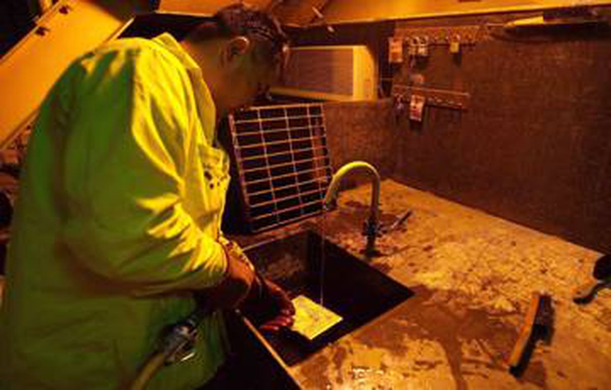 A worker cleans a freshly produced bar of gold at Centerra's Boroo mine in Mongolia