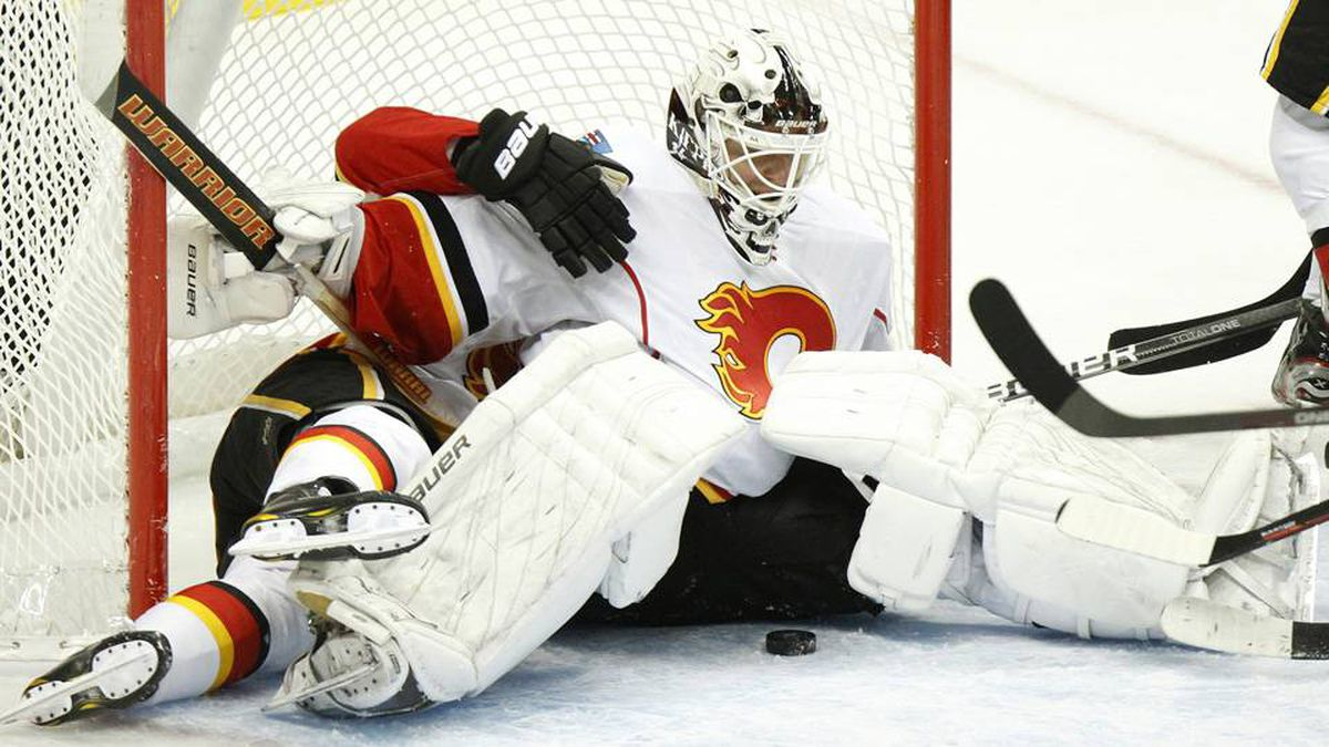 Calgary Flames goalie Miikka Kiprusoff guards the net after teammate Tom Kostopoulos fell behind him against the Colorado Avalanche during the third period of an NHL hockey game Sunday in Denver.