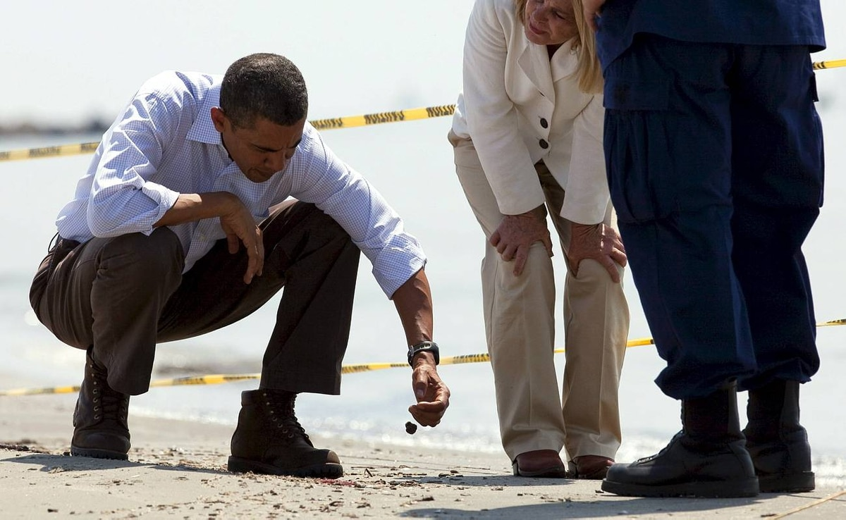 U.S. President Barack Obama, left, picks up a 'tar ball' on during a tour of areas impacted by the Gulf Coast oil spill on May 28.