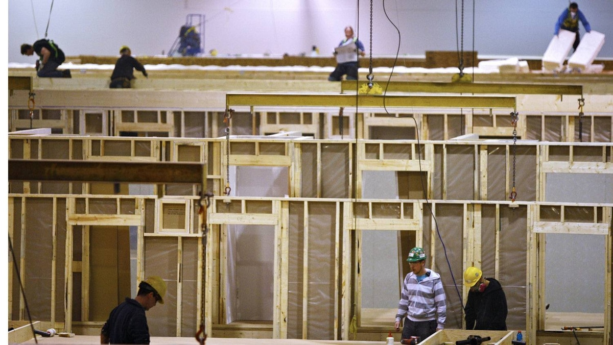 Construction tradesmen build portable housing for oil sands workers at the Atco Structures facility in Calgary. The manufacturing plant sprawls out across 250,000 square feet of concrete covered with stacks of drywall, boxes of spiced ash mouldings and bags of insulation batting.