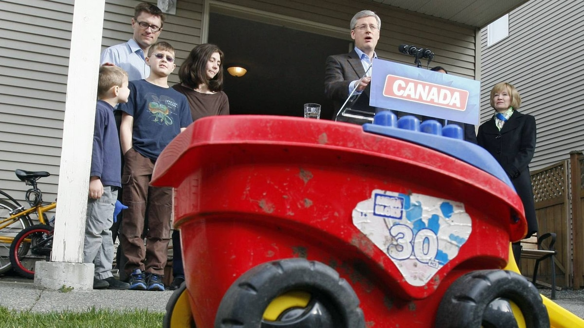 Prime Minister Stephen Harper speaks during a campaign stop in Saanich, B.C., on March 28, 2011 as his wife Laureen looks on with members of the Wellburn family.