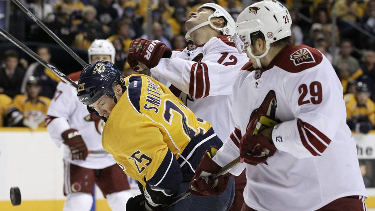 Nashville Predators centre Jerred Smithson (25) battles for the puck with Phoenix Coyotes left wing Paul Bissonnette (12) and centre Petteri Nokelainen (29) in the second period of an NHL hockey game on Oct. 13 in Nashville.