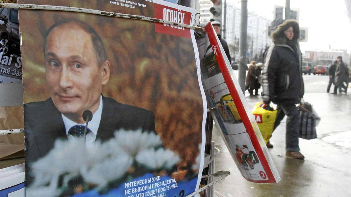 People walk past a news stand displaying a magazine showing Russian Prime Minister Vladimir Putin on the cover.
