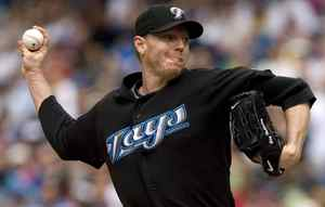 This is a July 19, 2009 file photo showing Toronto Blue Jays pitcher Roy Halladay throwing against the Boston Red Sox during the third inning of a baseball game in Toronto. Baseball closes in on its trade deadline, and the big question is the fate of Blue Jays ace Roy Halladay. (AP Photo/The Canadian Press, Darren Calabrese, File)