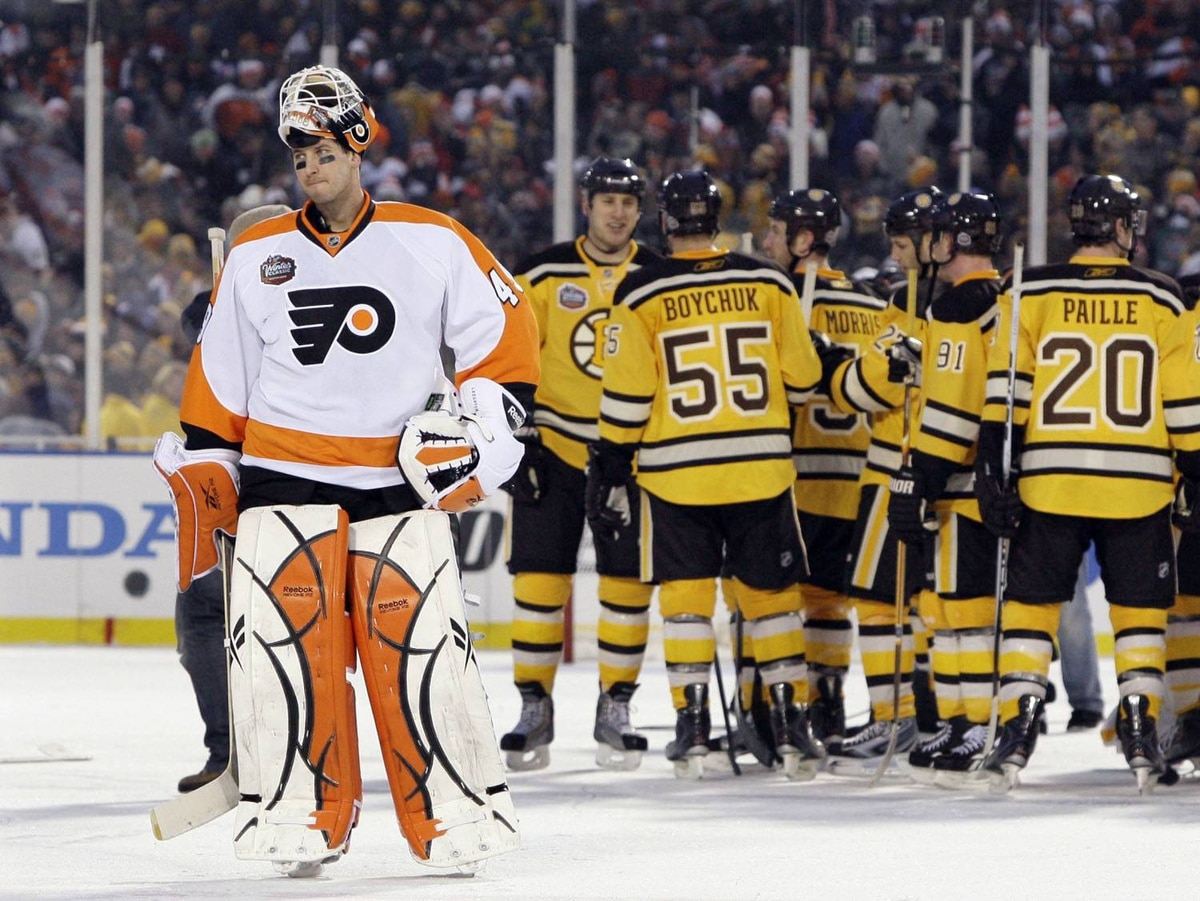 Philadelphia Flyers goalie Michael Leighton, left, skates off as the Boston Bruins celebrate their 2-1 overtime win in the New Year's Day Winter Classic NHL hockey game on the outdoor rink at Fenway Park in Boston, Friday, Jan. 1, 2010. (AP Photo/Elise Amendola)