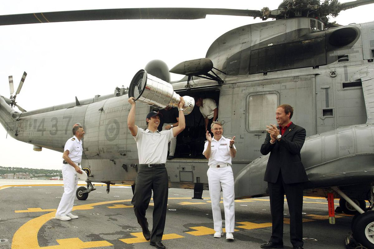 Crosby stepped off a Sea King helicopter with the cup to applause from Rear Admiral Paul Maddison, second right, and Defence Minister Peter MacKay, right.