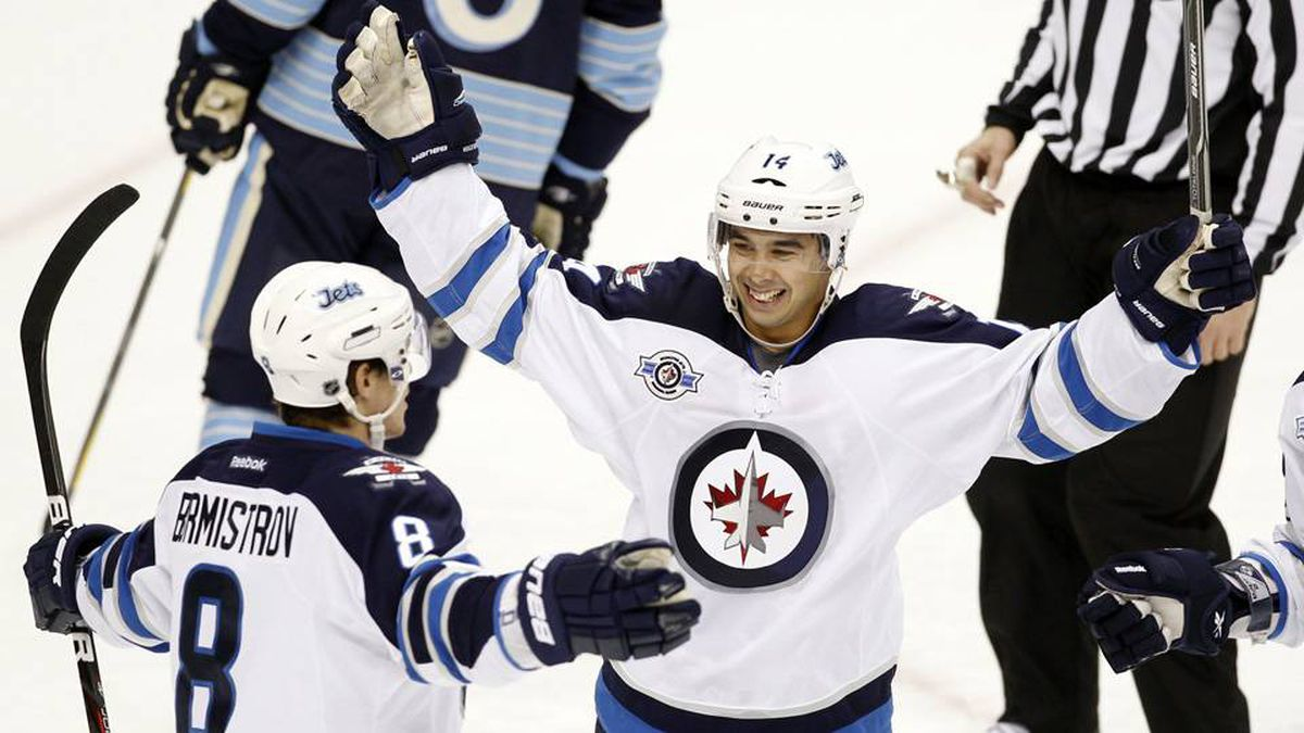 Winnipeg Jets Tim Stapleton (14) congratulates teammate Alexander Burmistrov (8) on his goal against the Pittsburgh Penguins in the first period of their NHL hockey game in Pittsburgh, Pennsylvania February 11, 2012.