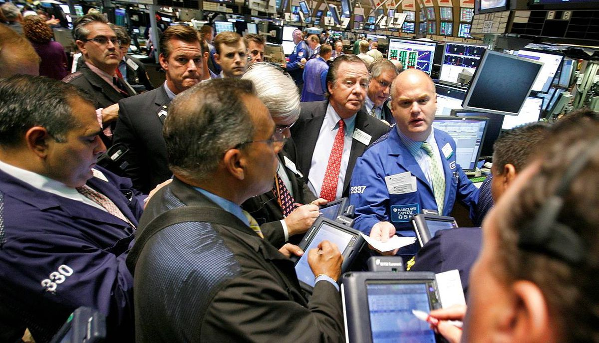 Specialist Evan Soloman, facing camera at right, is surrounded by traders on the floor of the New York Stock Exchange.