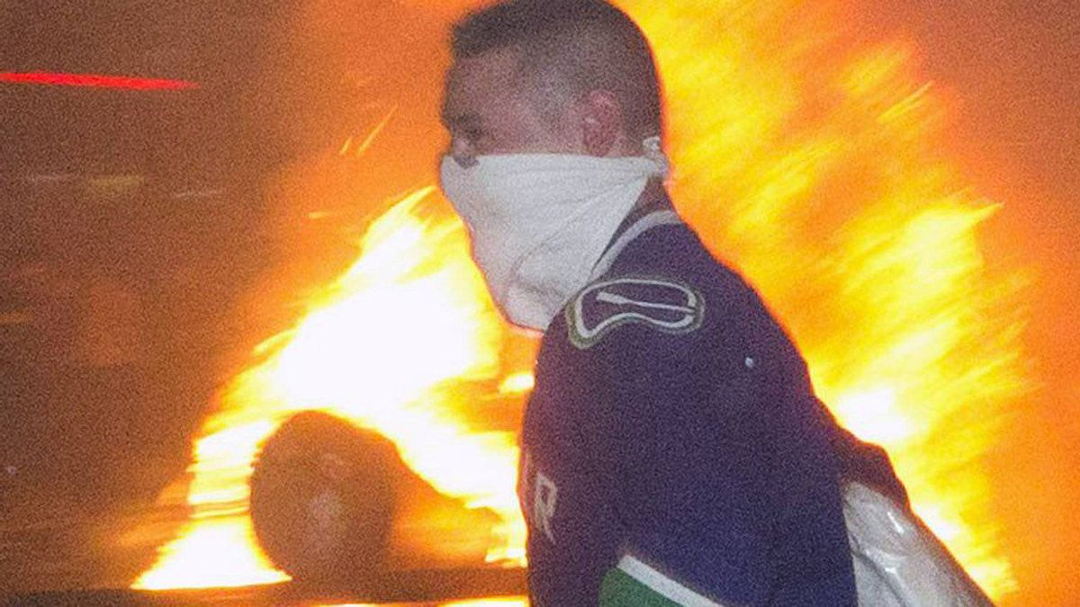 Looters from The Bay run past a burning car set off by rioters in Vancouver June 15, 2011.
