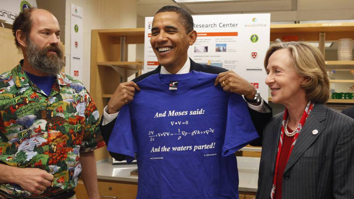 U.S. President Barack Obama holds up a t-shirt given to him by Mechanical Engineering Professor Alex Slocum (L) as Susan Hockfield, President of the Massachusetts Institute of Technology (MIT), takes him on a tour of the institution's research labs in Cambridge, Massachusetts, October 23, 2009.