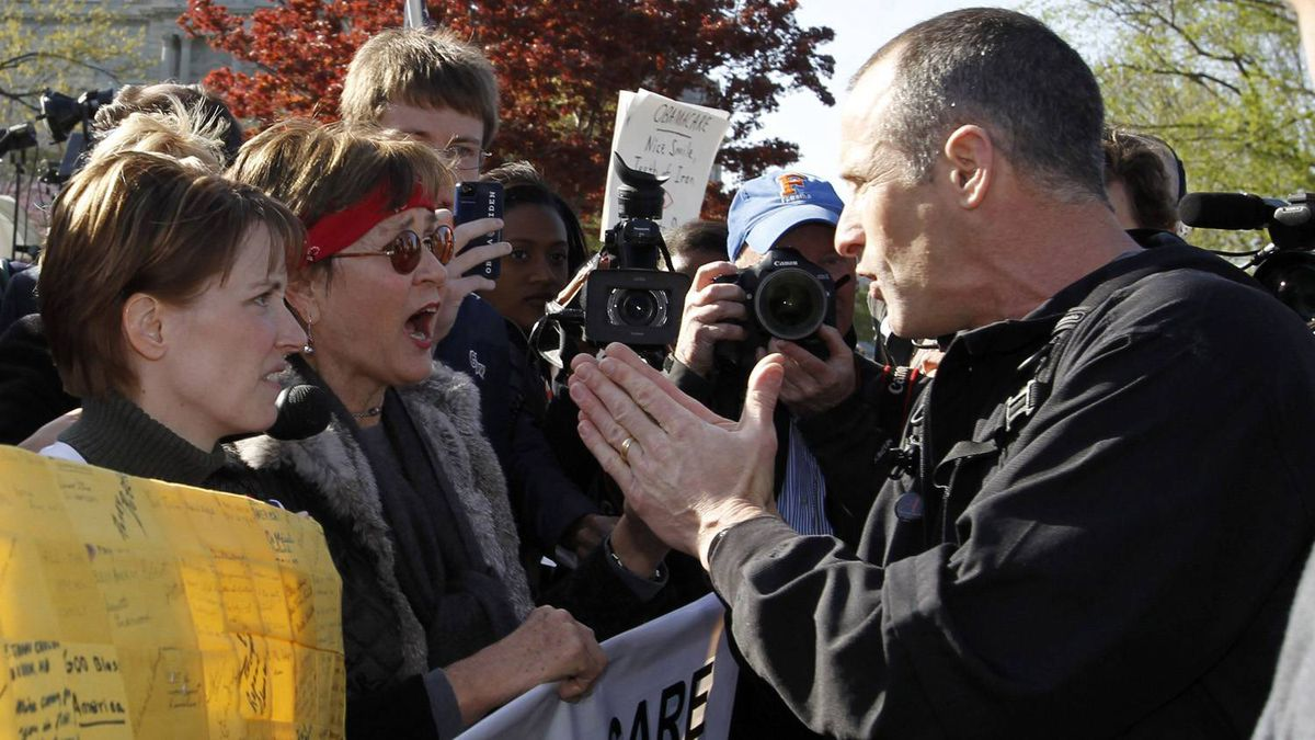 Protesters against President Barack Obama's healthcare law (L) clash with a man who supports it outside the Supreme Court during the first day of legal arguments over the Affordable Care Act in Washington March 26, 2012.