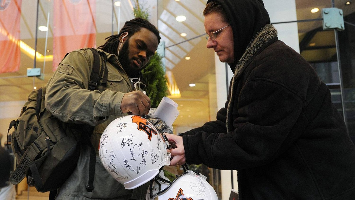 BC Lions' Solomon Elimimian (L) signs a football helmet for a fan before their team lunch in Vancouver, British Columbia November 24, 2011. The BC Lions will play the Winnipeg Blue Bombers in the CFL's 99th Grey Cup football game this Sunday, November 27, 2011. REUTERS/Todd Korol