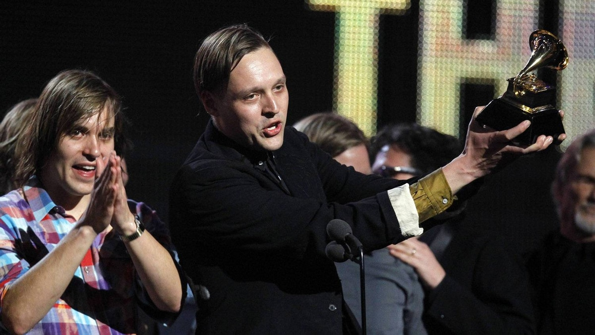 "Edwin Butler of Canadian band Arcade Fire holds up the Grammy for Album of the Year for ""The Suburbs"" at the 53rd annual Grammy Awards in Los Angeles, California February 13, 2011."