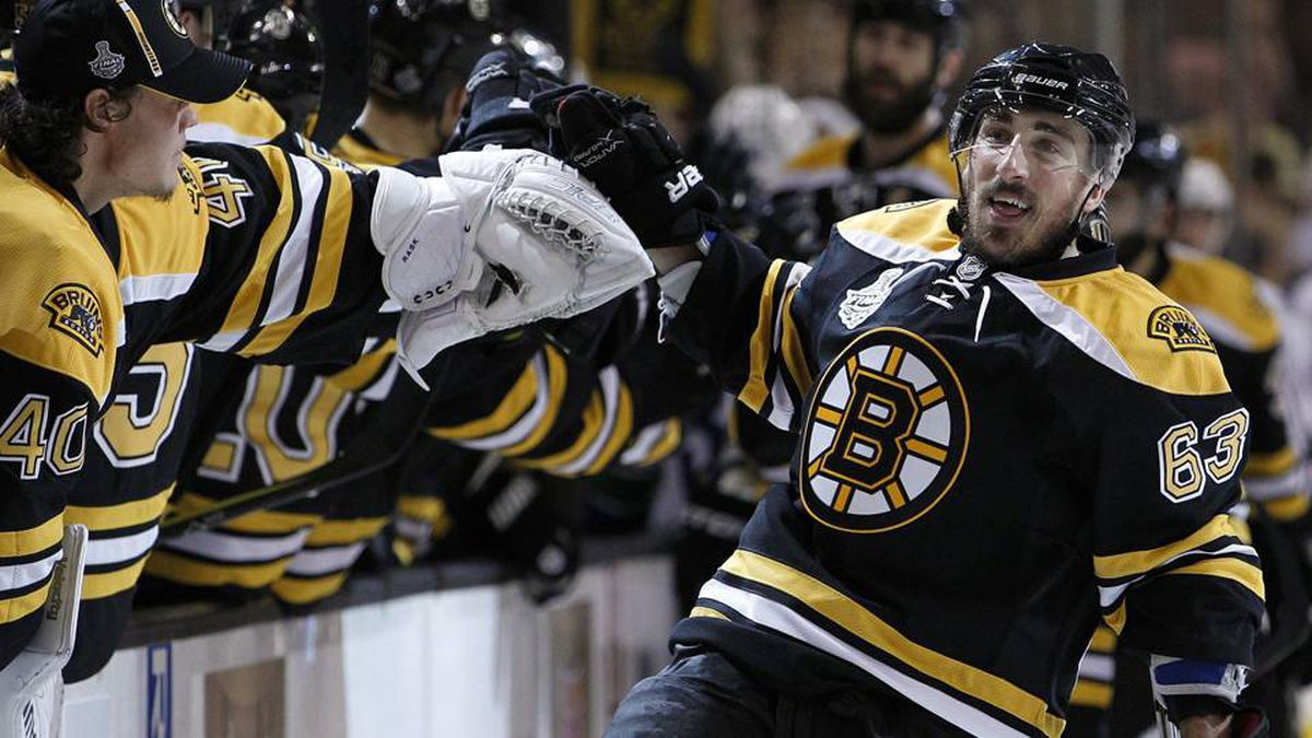 Boston Bruins left wing Brad Marchand high-fives teammates on the bench after scoring against the Vancouver Canucks in the first period.