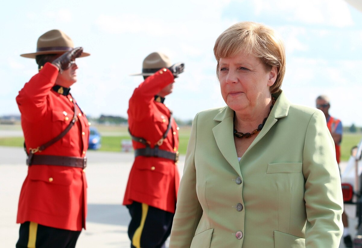 Mounties salute German Chancellor Angela Merkel as she arrives at the Canada Reception Centre in Ottawa, Wednesday, August 15, 2012.