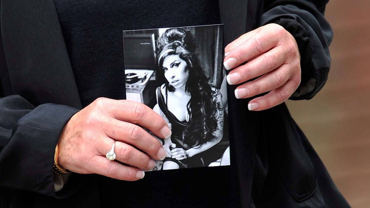 A mourner holds a photograph of Amy Winehouse on the way to a funeral service for singer Amy Winehouse at Edgwarebury Lane cemetery on July 26, 2011 in London, England.