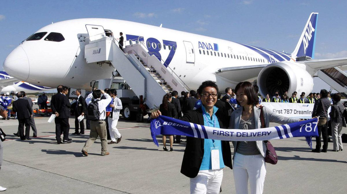 Passengers on the Boeing 787 Dreamliner's first commercial flight pose for pictures before boarding at Tokyo's Narita airport on Wednesday, Oct. 26. Some aviation enthusiasts paid thousands of dollars to be on the carbon-composite design plane, which its maker says is lighter, more economical to fly and more comfortable than its metal rivals.