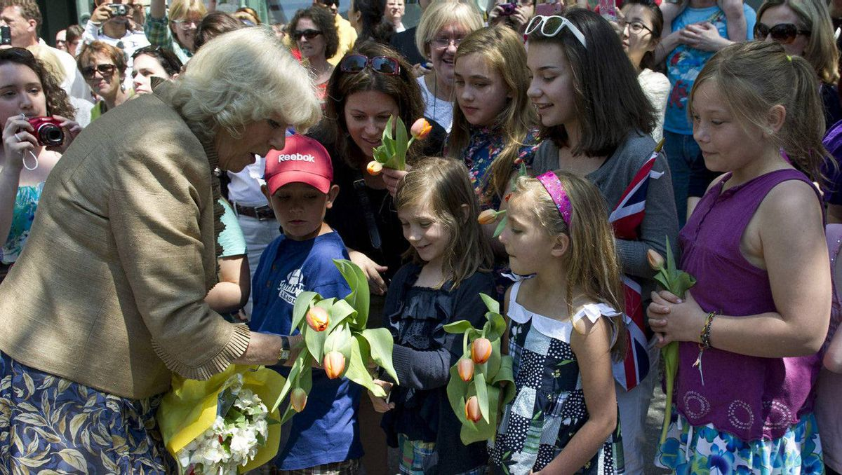 The Duchess of Cornwall is presented with flowers by a group of young girls during a walk about Saint John, N.B., on Monday, May 21, 2012. The royal couple are on a three-day visit to Canada to mark the Queen's Diamond Jubilee.