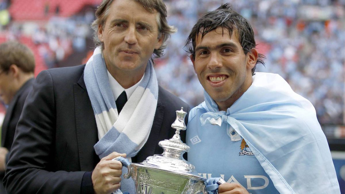 Manchester City's manager Roberto Mancini (L) and Carlos Tevez hold the trophy after defeating Stoke City in their FA Cup final soccer match at Wembley Stadium, in London May 14, 2011.