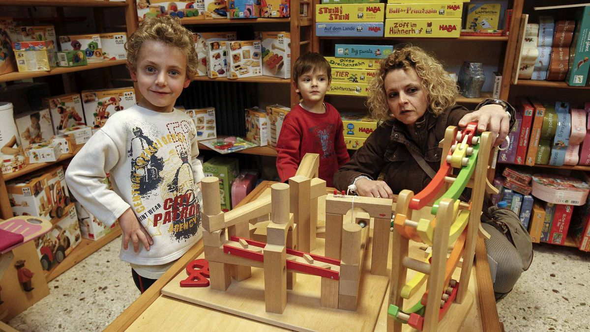 "Employed mother of three, Zoe Makri, 40, plays with her sons Marios, left, and Michalis inside the ""Come and See"" toy shop in the Athens suburb of Glyfada, November 25, 2011. Ms. Makri said she will do just basic Christmas shopping this year to cover her children's needs instead of buying everything she would like."