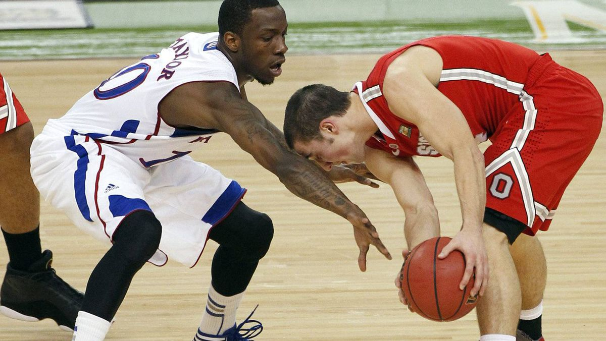 Kansas' Tyshawn Taylor, left, tries to steal the ball from Ohio State's Aaron Craft during the first half of an NCAA Final Four semifinal college basketball tournament game Saturday, March 31, 2012, in New Orleans. (AP Photo/Bill Haber)