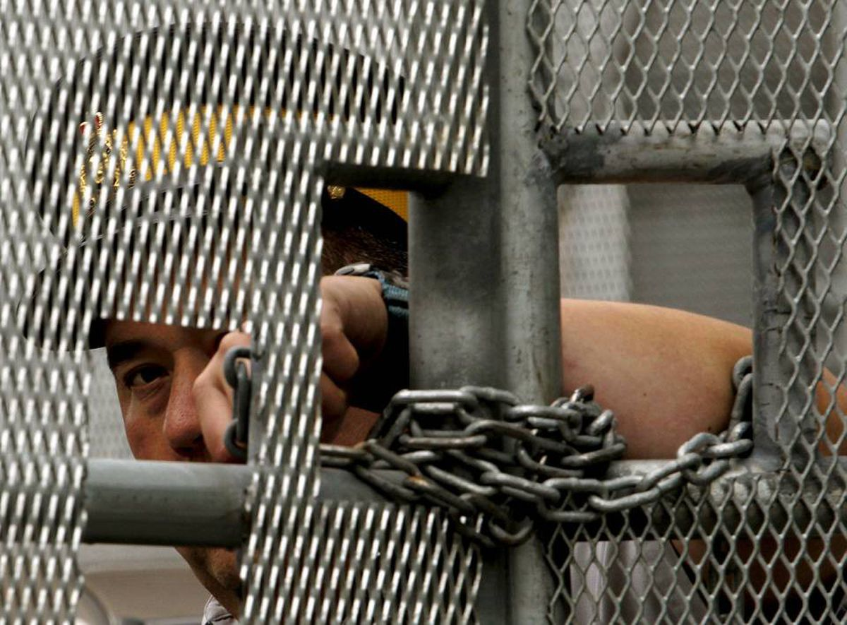 A police officer peers out through a locked gate inside the perimeter fence leading to the Metro Toronto Convention Centre G20 Summit site in Toronto June 26, 2010.