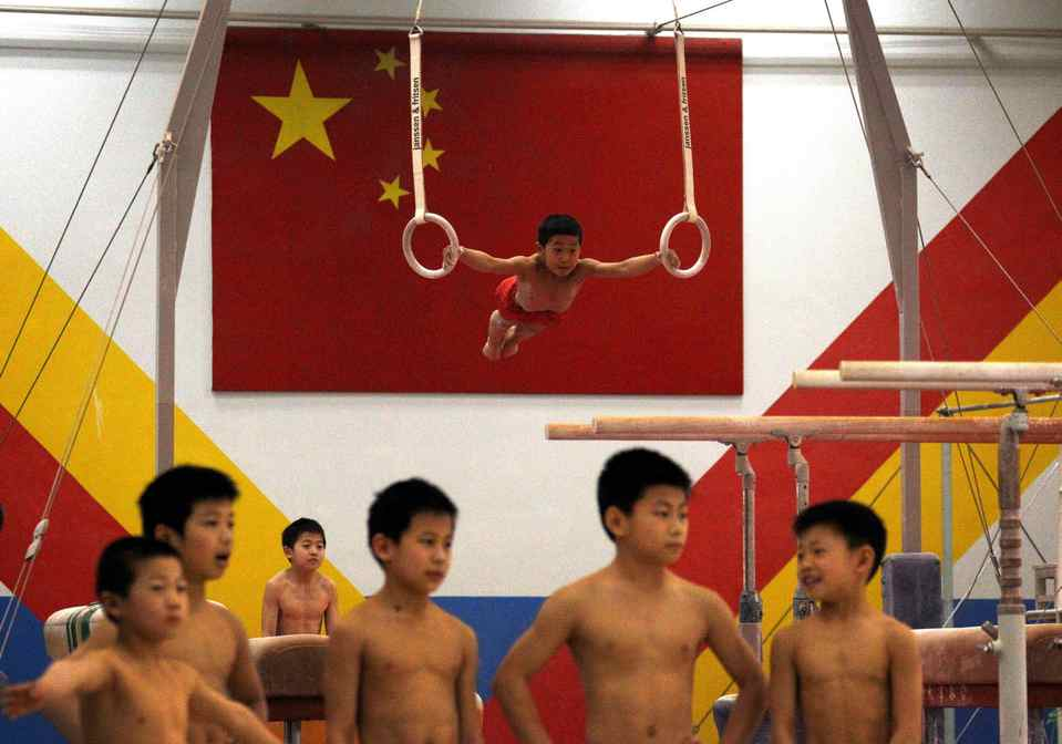 Young gymnasts stand together as a classmate hangs from gymnastic rings in front of a Chinese national flag. Children are handpicked from around China and sent to be trained as the next generation of Olympic champions for sports including table tennis, badminton, weightlifting, gymnastics, volleyball, boxing and tae kwon do.