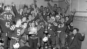 Toronto. November 27, 1948. Calgary Stampeders celebrate in their dressing room after defeating the Ottawa Roughriders to win the Grey Cup. Holding the Grey Cup is Coach Les Lear (helmet) and centre Chuck Anderson who was the outstanding player on the field. Other players who can be identified are (42) Woody Strode, (5) Harry Hood and (49) Dave Tomlinson.
