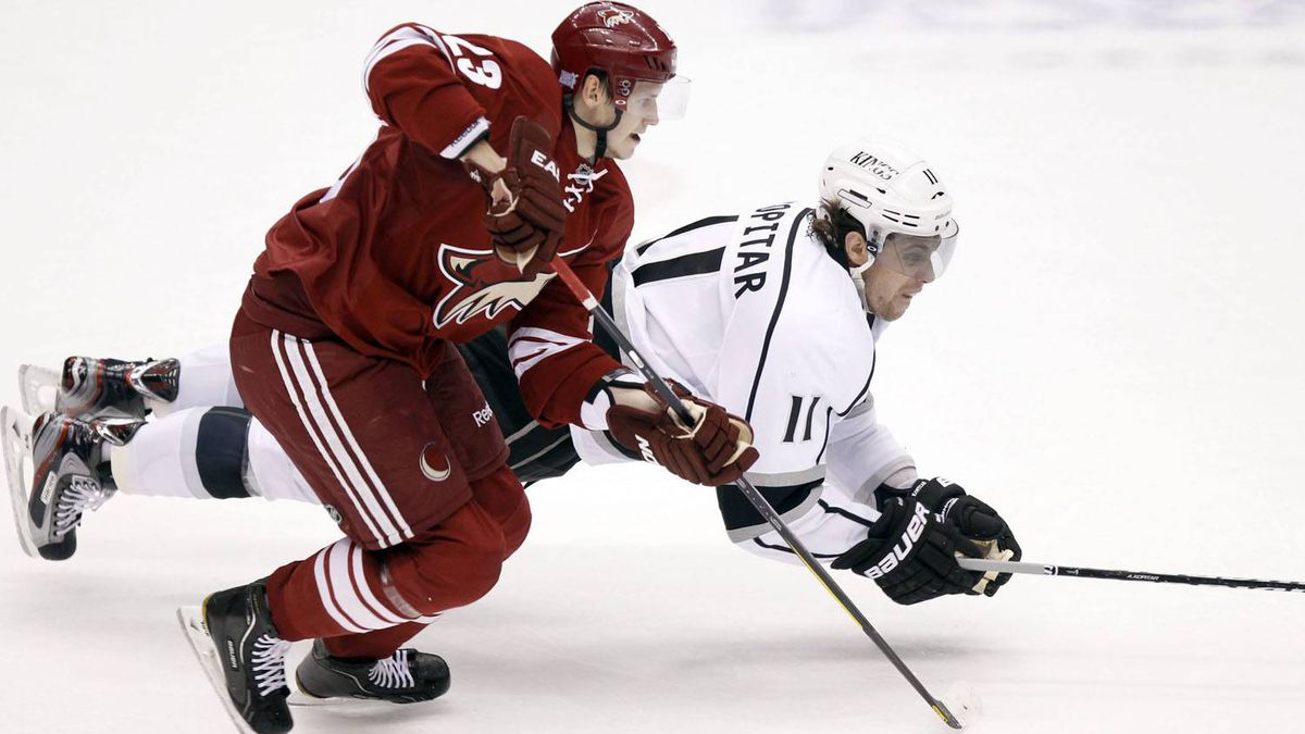 Los Angeles Kings' Anze Kopitar (11), of Slovenia, dives for the puck behind Phoenix Coyotes defenseman Olive Ekman-Larsson, left, of Sweden, in the second period of an NHL hockey game Saturday, Oct. 29, 2011, in Glendale, Ariz. The Coyotes won 3-2 in overtime. (AP Photo/Paul Connors)