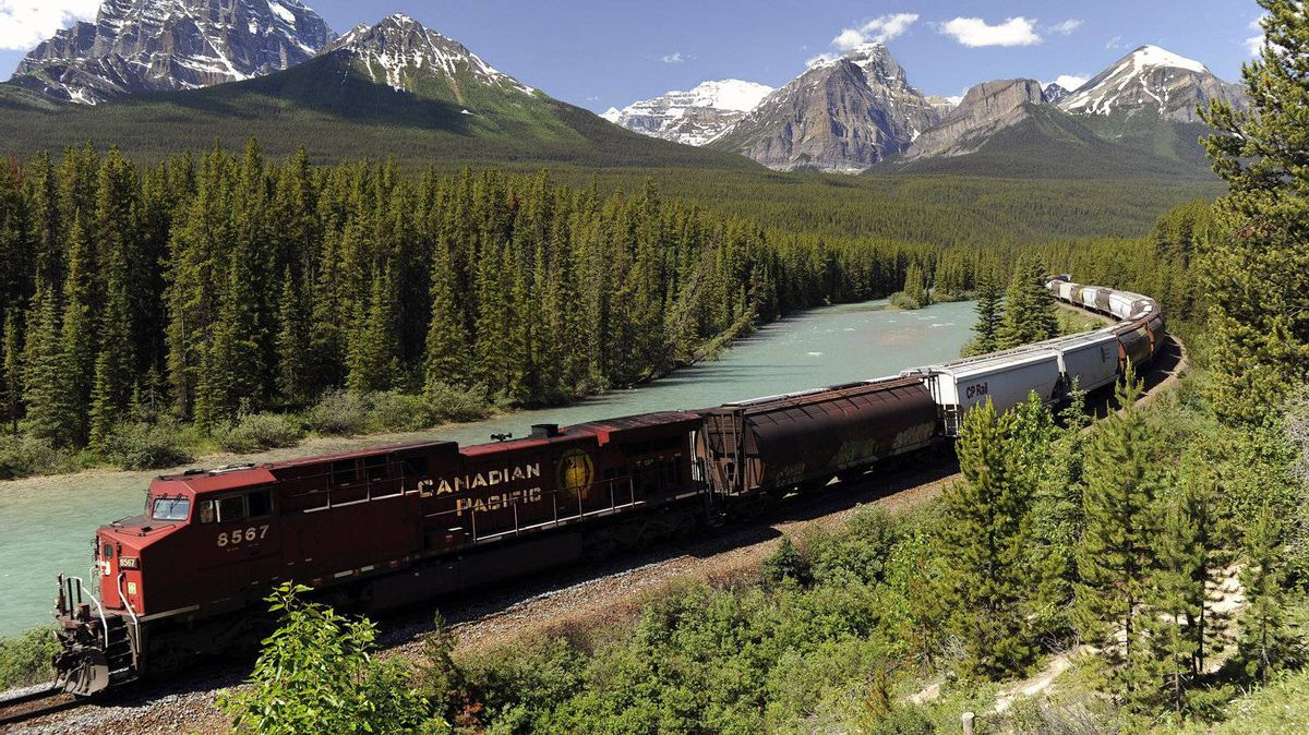 A Canadian Pacific Railway freight train runs along the Bow River and distant Rocky Mountains on the main line near Lake Louise, Alta.