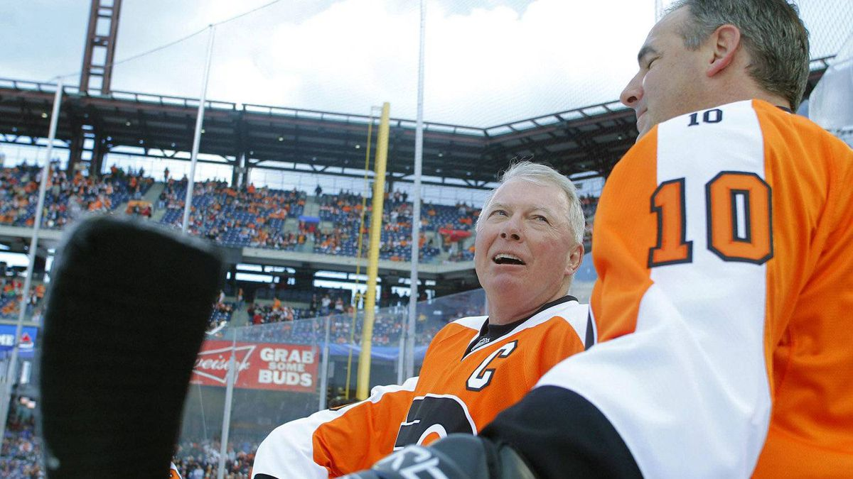 b Clarke, left, and John LeClair, of the Philadelphia Flyers alumni team, talk during warmups. (AP Photo/Tom Mihalek)
